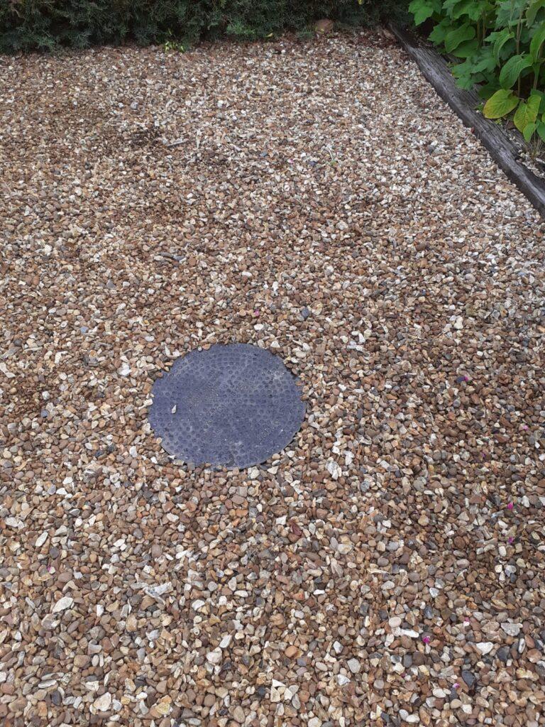 Manhole cover set in gravel drive